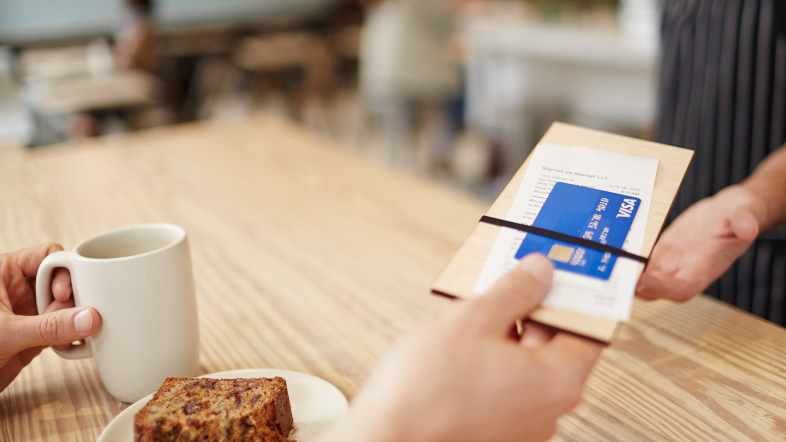 A customer sitting at a table with a mug and pastry handing the waiter the check with a Visa card.