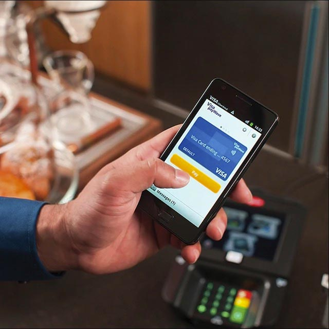 Person using Visa Paywave on a mobile phone.