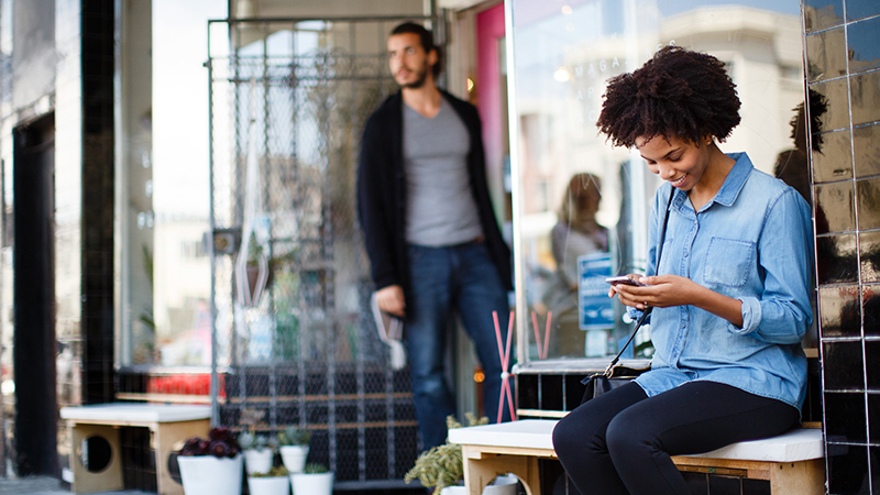 Woman shopping on her phone sitting on a bench