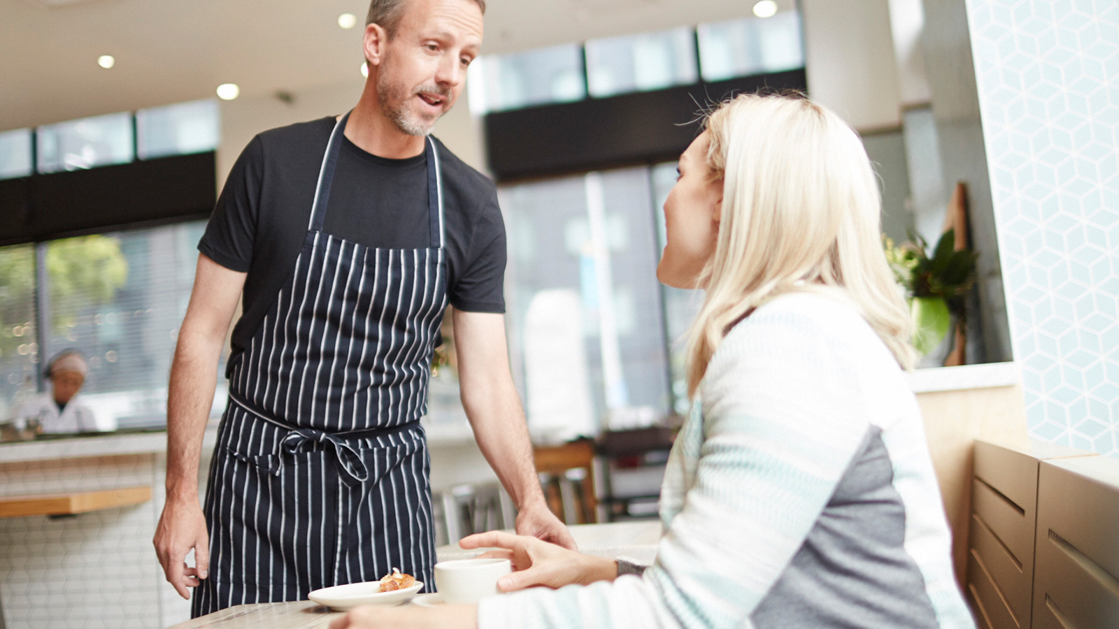 A man talking to a woman seated at a table in a café.